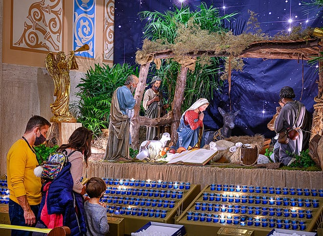 A family stands in front of a nativity scene in the Cathedral Basilica of St. Augustine on Monday.