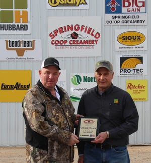 Springfield Coop Creamery General Manager Steve Helget presented Jerry Haala with a plaque in honor of his 45 year career in feed sales on Haala's retirement day, Friday, Dec. 11.