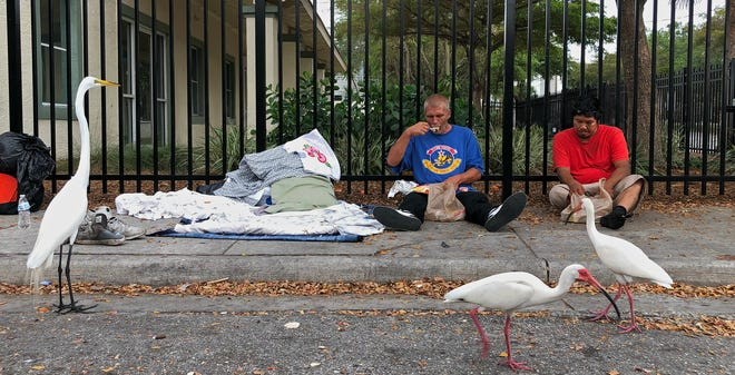 Homeless and looking for work, Roger and John, on right, eat meals provided by Streets of Paradise just outside of Sarasota's Salvation Army at 1400 10th St. in Sarasota.