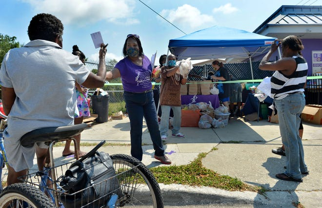 """Second Chance Last Opportunity founder April Glasco, center, at a food giveaway in 2020. """"Today, the need is still growing,"""" Glasco said."""