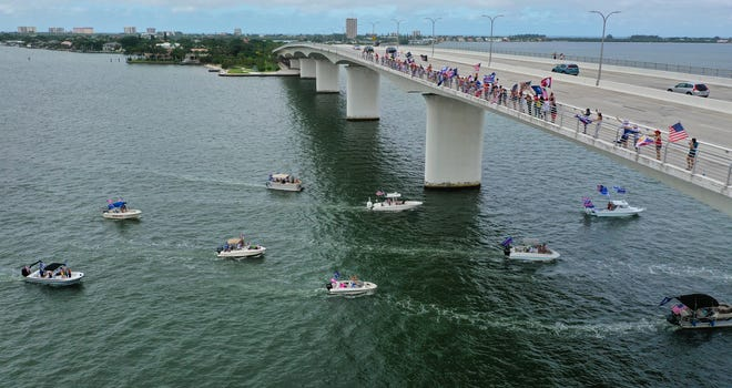 """Donald Trump supporters line up along the John Ringling Causeway, in Sarasota, as about three dozen boats in the """"Rescue America Boat Flotilla"""" pass through Sarasota Bay in September 2020."""
