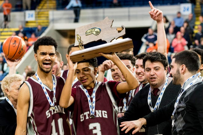 Avery DeBrito lifts the Div. 3 State Champion trophy following the team's 80-64 victory over Oxford.