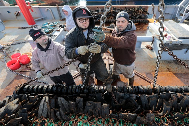 (l to r) Captain Rui Branco gives Giovanni Pinto, mate, and Fernando Goncalo, deckhand, a hand installing a new chain on one of the two dredges aboard the scalloper Elizabeth & Niki docked in New Bedford.