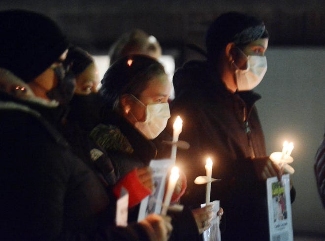 Mourners hold candles and photos of homeless people who died in 2020 Monday at the Homeless Persons Memorial in Norwich. [John Shishmanian/ NorwichBulletin.com]