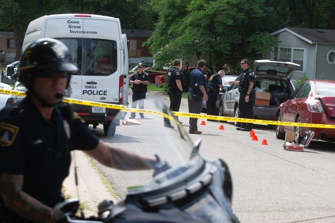 Topeka police officers work at the scene of a homicide in the 3800 block of S.W. South Park Avenue in August.
