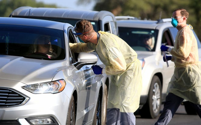 Scott Pauly, a family practitioner at the Hutchinson Clinic, takes a throat swab sample during a drive-through COVID-19 testing event. Statewide, testing for COVID-19 has dropped in recent weeks.