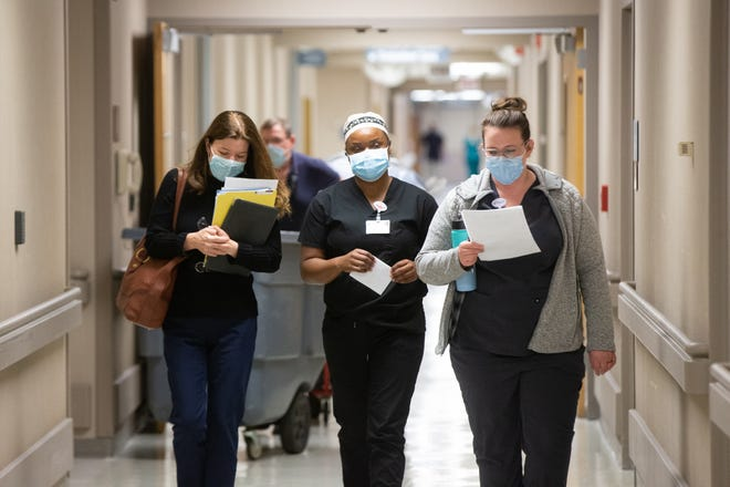 Salena Gillum, left, administrative director of medical surgical and critical care at Stormont Vail, walks down a hallway with nurses on Nov. 18 as COVID cases put the hospital at capacity.