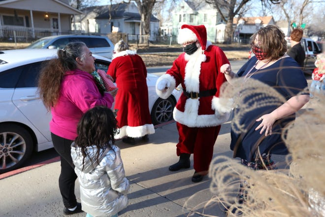 Santa Claus and a Quincy Elementary teacher hand gifts to Rosa Sazo and her grandchildren Nayden, a first-grader at the school, and 4-year-old Yareli Monday afternoon at a drive-thru gift distribution at the school. The event came together in a week, said principal Katie Sonderegger, as part of a bid to keep the school's holiday tradition going.