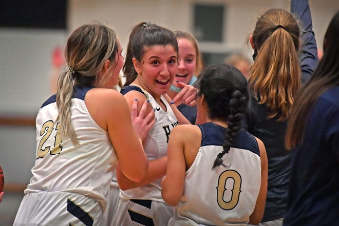 Hayden's Macy Smith, center, is mobbed by teammates Carly Stuke (21) and Noelia Cruz (0) after sinking two free throws with one second left to give the Wildcats a 37-36 win over visiting Seaman on Monday night.