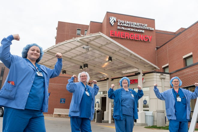 From left, Tamra Simpson, resident nurse; Emily Tappan, surgical tech; Donna Mears, surgical tech; and Patti Chartier, resident nurse, show their strength in front of The University of Kansas Health System St. Francis Campus.