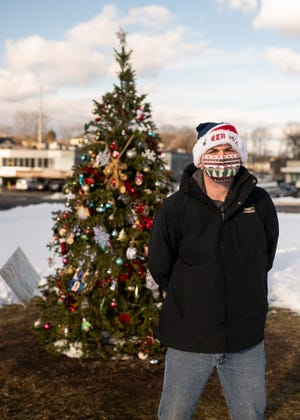 Burncoat neighborhood resident Brian Underwood stands in front of the holiday wishing tree at East Mountain and Burncoat streets in Worcester. He helped organizer the effort to decorate the fir with ornaments placed by fellow residents.