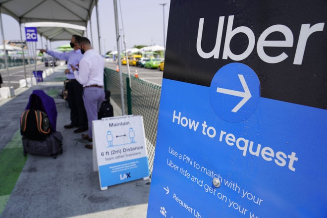 Travelers request wait for an Uber ride at an airport.