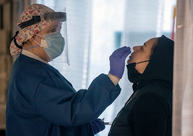 Nurse Denise Khalili, left, tests Adarita Rivera of Webster for COVID-19 by swabbing her nose at a free testing site inside Mercantile Center in Worcester on Tuesday.
