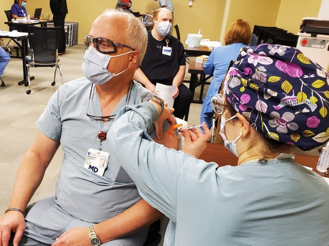 Dr. Kenneth Fath gets the first injection of the Pfizer COVID-19 vaccine at Alamance Regional Medical Center from Sarah Block.