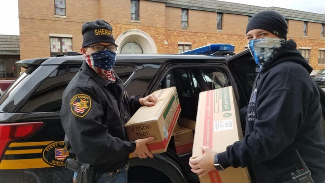 Tuscarawas County sheriff's Deputy Cole Morris (left) and New Philadelphia police Officer Chad Dorsey load artificial trees for delivery to families as part of the Christman with a Cop effort of Fraternal Order of Police Tuscora Lodge No. 4.