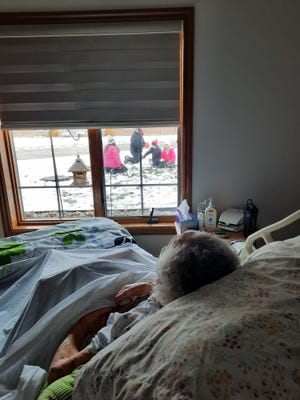Betty McMullen watches the outside activity from her bed at Park Village.