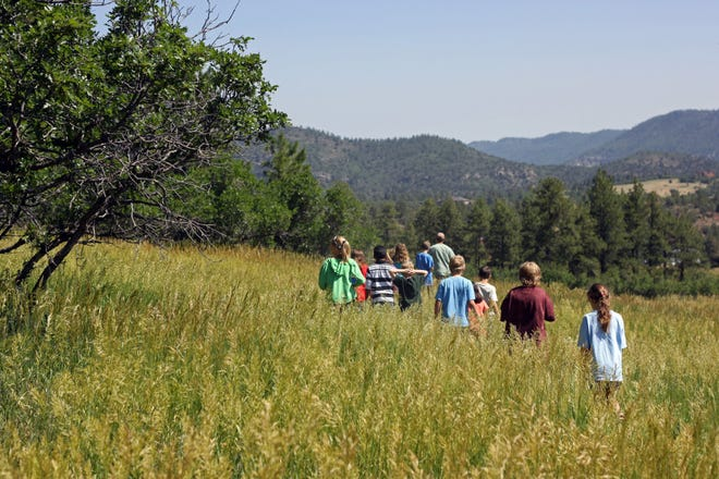 Nature and Wildlife Discovery Center program participants hike through a meadow in Pueblo Mountain Park.