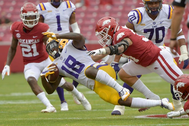 LSU running back Chris Curry (18) spins away from Arkansas defender Grant Morgan (31) during the first half of an NCAA college football game Saturday, Nov. 21, 2020, in Fayetteville. Morgan was named among the best linebackers in the SEC for 2020.