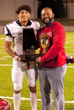 Holt native Mario White holds the 2020 AISA Class AAA football championship trophy he won as head coach at Pike Liberal Arts School. He's shown, post-championship game, with his son at Pike quarterback Ples White III who has signed a baseball scholarship with Florida State.