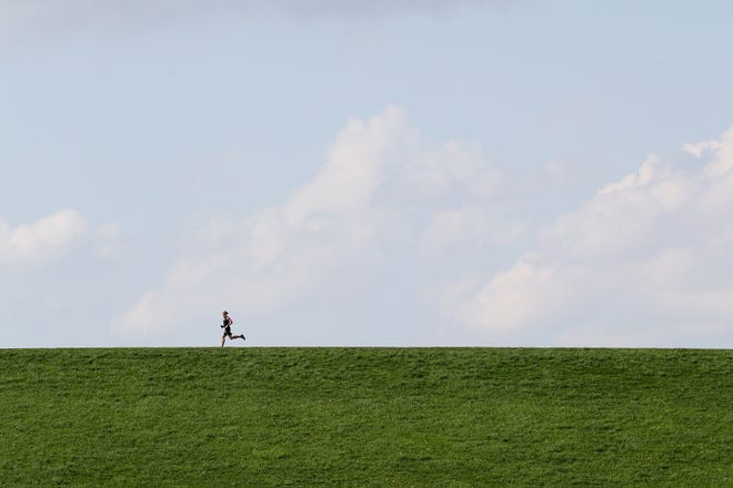 A runner makes his way across a walking path April 7 near the Alum Creek dam in Westerville.