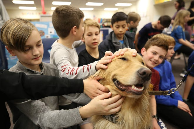 Edison Intermediate/Larson Middle School fourth-grader Hudson Barber, 10, and others pet Columbus Division of Police therapy dog Ollie during the therapy-dog unit's visit March 13.