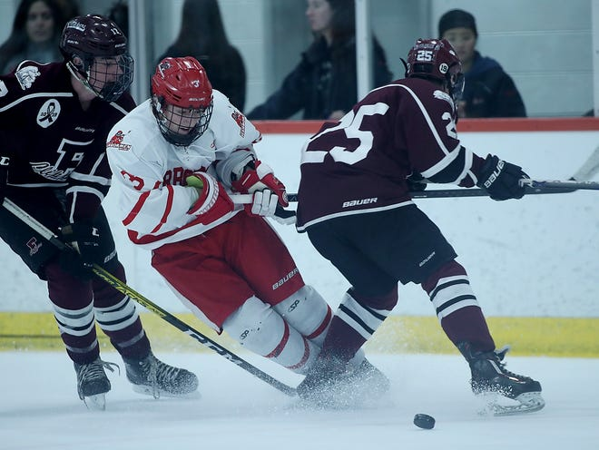 Hingham's Lars Osterberggets tripped up by Falmouth's Aaron Schlezinger while trying to elude him with a move during third period action of their game in the Division 1 South quarterfinal at Gallo Ice Arena on Saturday, Feb. 29, 2020. [Wicked Local Staff Photo/ Robin Chan]