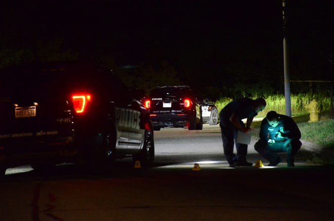 Police collect evidence at the scene of the shooting.