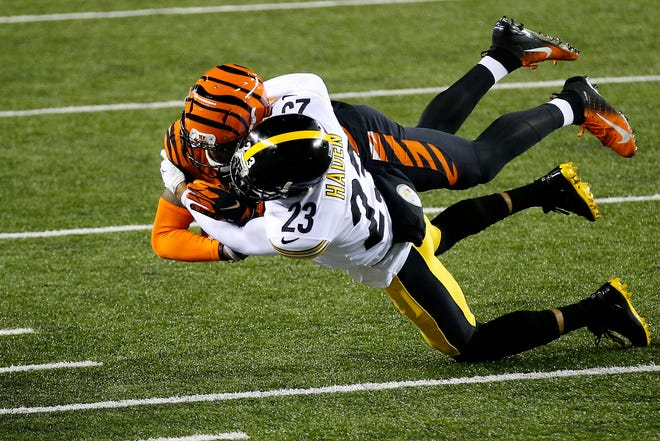 Pittsburgh Steelers cornerback Joe Haden (23) throws down Cincinnati Bengals wide receiver Tee Higgins (85) after a catch in the first quarter of the NFL 15 game between the Cincinnati Bengals and the Pittsburgh Steelers at Paul Brown Stadium in downtown Cincinnati on Monday, Dec. 21, 2020. The Bengals led 17-0 at halftime.