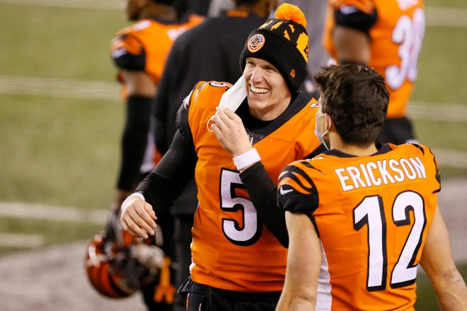 Cincinnati Bengals quarterback Ryan Finley (5) smiles as he talks with wide receiver Alex Erickson (12) as the final minute runs off the clock in the fourth quarter of the NFL 15 game between the Cincinnati Bengals and the Pittsburgh Steelers at Paul Brown Stadium in downtown Cincinnati on Monday, Dec. 21, 2020. The Bengals beat the Steelers, 27-17, on Monday Night Football.