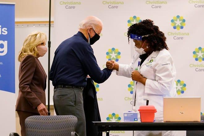 Presiden terpilih Joe Biden bentrok dengan perawat praktisi Tabe Mase setelah menerima dosis pertama vaksin virus corona di Rumah Sakit ChristianaCare Christiana di Newark, Del., Senin, 21 Desember 2020, saat Jill Biden melihat.