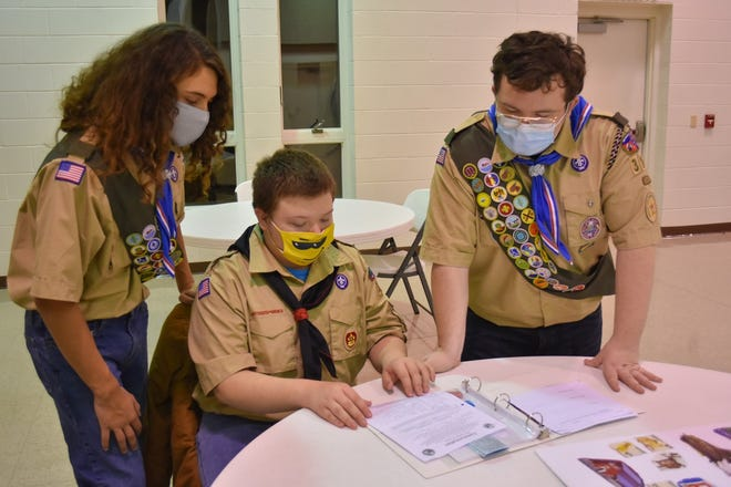 Aden Carter, left, and Alan Carter III, right, both earned Eagle rank. Here, they help their brother, Anthony Carter, with a project during a scout meeting at Grace Lutheran Church in Elmore on Dec. 20.