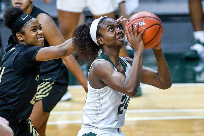 Michigan State's Nia Clouden, right, scores as Oakland's Brianna Breedy defends during the third quarter on Tuesday, Dec. 22, 2020, at the Breslin Center in East Lansing.
