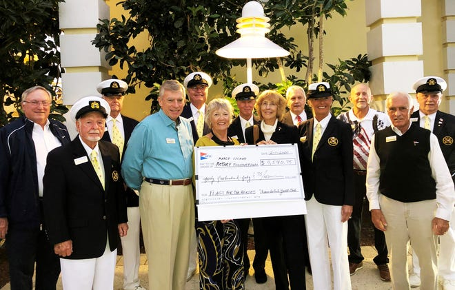 "Holding the check representing Marco Island Yacht Club's donation to the Noon Rotary for its ""Flags for Heroes"" program is Yacht Club Secretary Vicki Bretthauer, left, and Rotary Club President Linda Sandlin. To the left of the check is Yacht Club Chairman of the Board Dave Everitt and to the right of it is Dwyn von Bereghy, Chair of the Yacht Club's Community Outreach Committee. Surrounding them all are several of the Yacht Club's many U.S. Service Veterans."