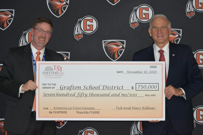 Grafton School District Superintendent Jeff Nelson, left, accepts a check for $750,000 from Ted Kellner. Kellner and his wife, Mary,  donated the money toward Grafton High School's athletic facility improvement projects.