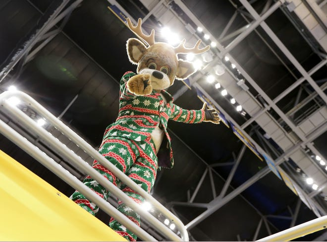 Bango, the Milwaukee Bucks' mascot, sports a festive holiday suit while posing for the camera at Fiserv Forum in Milwaukee on Tuesday, Dec. 22, 2020. While preparations were underway for the home opener on Christmas Day, only a few dozen people inside the arena will see the whole production when Fiserv Forum opens for the first time for the Bucks 2020-'21 season.