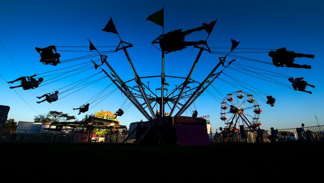 Children ride the carnival rides as the sun sets on the Autauga County Fair in Prattville, Ala., on Tuesday evening October 13, 2020.