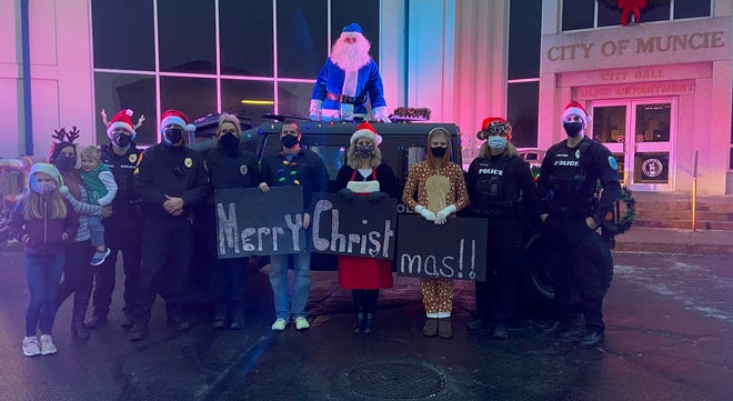 Some of the Muncie Police Department take a photo before delivering gifts to families in need over the weekend.