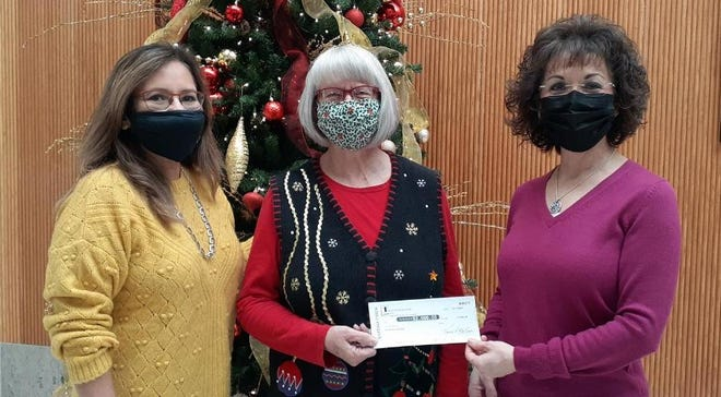 Cheryl Lenhardt (center), of St. Vincent de Paul, received a check from bank officials Rosa Perez (left) and Teresa Molina.