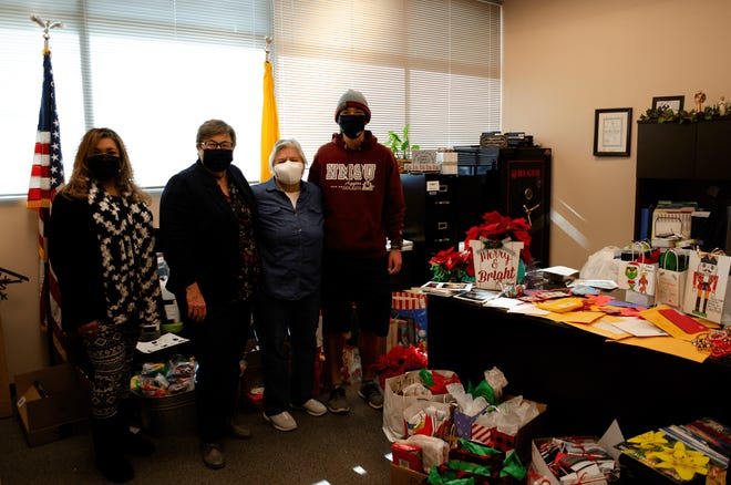 Andrea Ferrales-Narvaez, Doña Ana County Sheriff Kim Stewart, Rosa Torres and Joseph Rath pose Monday, Dec. 21 with the cards and gifts donated for Doña Ana County seniors in facilities.