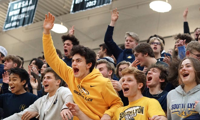 South Lyon High fans show their exuberance after the varsity basketball team hits a triple point against East on Jan. 10, 2020.