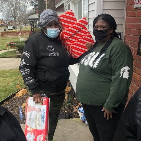 Sharon Kilgore, right, and Jasmine Mahone, Brilliant Detroit volunteers, distribute gifts donated from The Robot Garage to families.