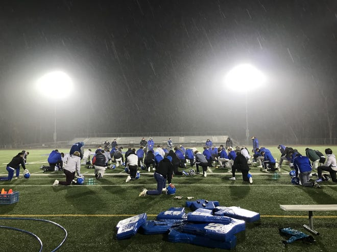 Detroit Catholic Central football gathers after its first practice back after a month-long season postponement.