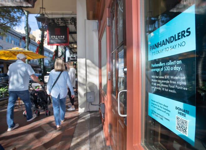 """A """"Panhandlers: It's Okay to Say No"""" sign hangs in a window along Palafox Place in downtown Pensacola on Tuesday."""