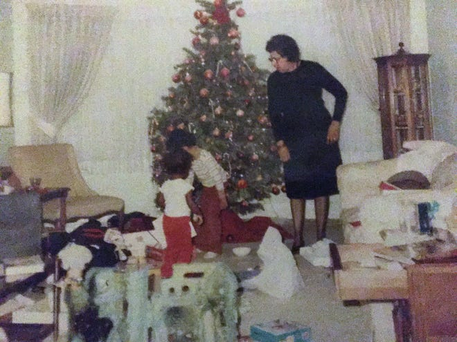 Greg Moore and his cousin tear through presents on Christmas Day in the 1980s at his grandmother's house in Detroit while she looks on.
