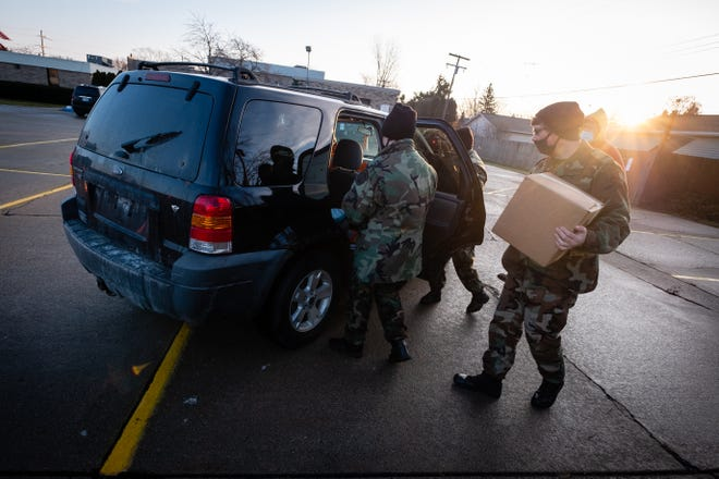 A group of Port Huron Young Marines load bags and boxes of food into vehicles on the Salvation Army's distribution day Tuesday, Dec. 22, 2020, in Port Huron.