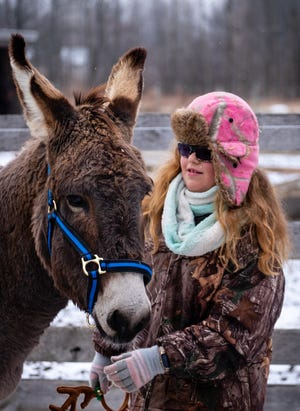 Julianna Mazzarini, 8, puts reindeer antlers on Hee Haw, a rescued donkey, Thursday, Dec. 17, 2020, at The Mustang Acres Farm. The 9-year-old donkey was rescued from a kill pen in November.