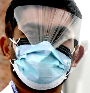 Frontline health worker Dr. Hardik Patel wears some of his personal protective equipment outside WellSpan York Hospital Tuesday, Dec. 22, 2020. He provides care to about 23COVID-19 patients each day. Bill Kalina photo