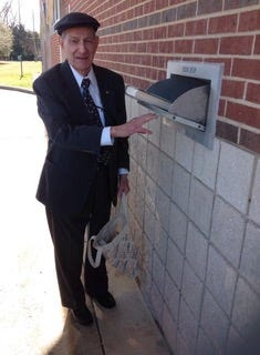 Allan Lazarus returns a book at the Broadmoor Library drive-through.