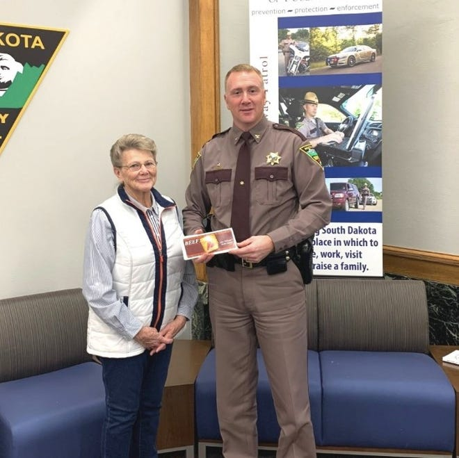 Nancy Montross, who founded Beef Bucks, Inc. with her husband Bob, presents the organization's donation to Colonel Rick Miller, Superintendent of the Highway Patrol.