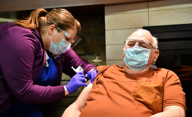 Associate Nurse Manager Crystal DeMoss gives Curtis Sannerud the first COVID-19 vaccine for a patient Tuesday, Dec. 22, 2020, in the Community Living Center at the St. Cloud VA Health Care System.  Sannerud, 90, is a Korean War-era Veteran who was admitted to the CLC in 2015.